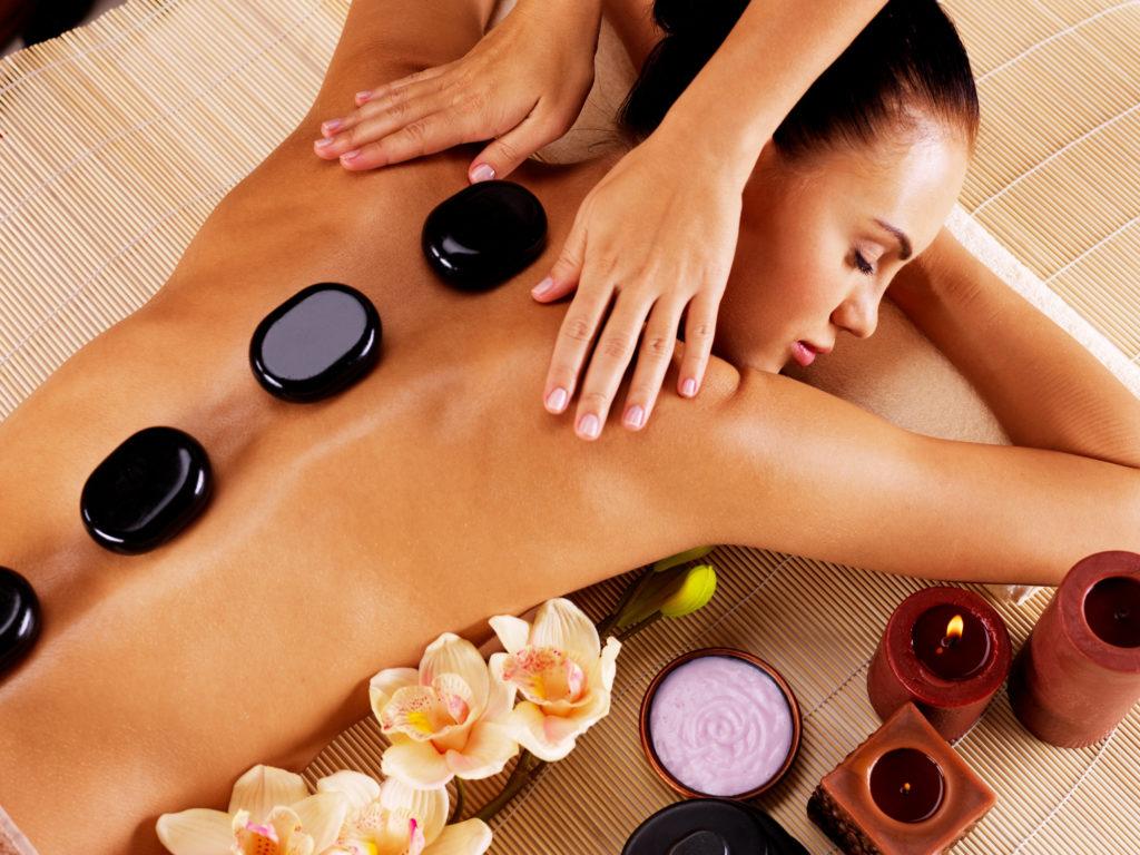 Adult woman having hot stone massage in spa salon. Beauty treatment concept.