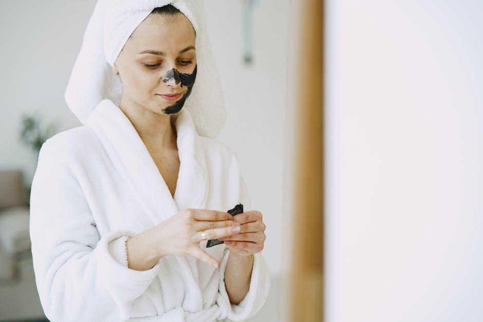 women applying face mask in a bath robe