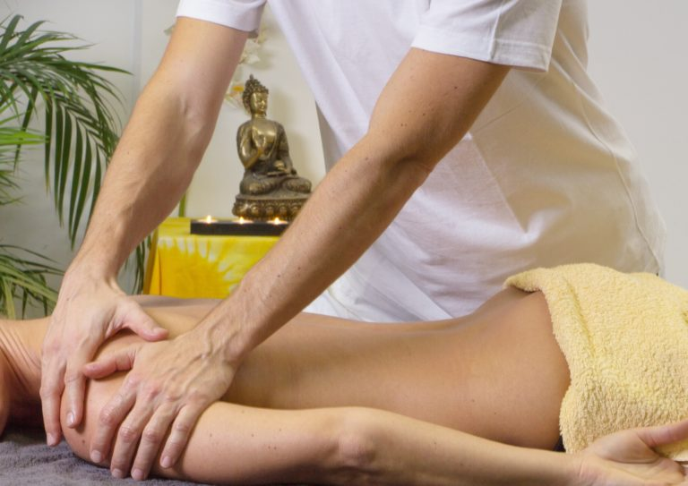a women getting massaged by another person on a massage table